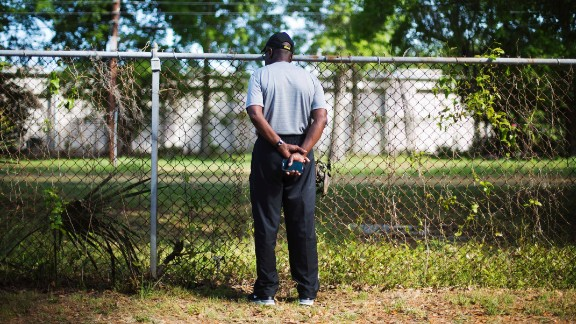Joe Gilliard looks over a fence April 9, 2015, at the spot where Walter Scott was shot and killed by a police officer April 4 in North Charleston, South Carolina. The officer, Michael Slager, has been charged with murder in the fatal shooting of Scott, an unarmed 50-year-old. Video captured by a bystander showed Slager shooting Scott as he ran away.