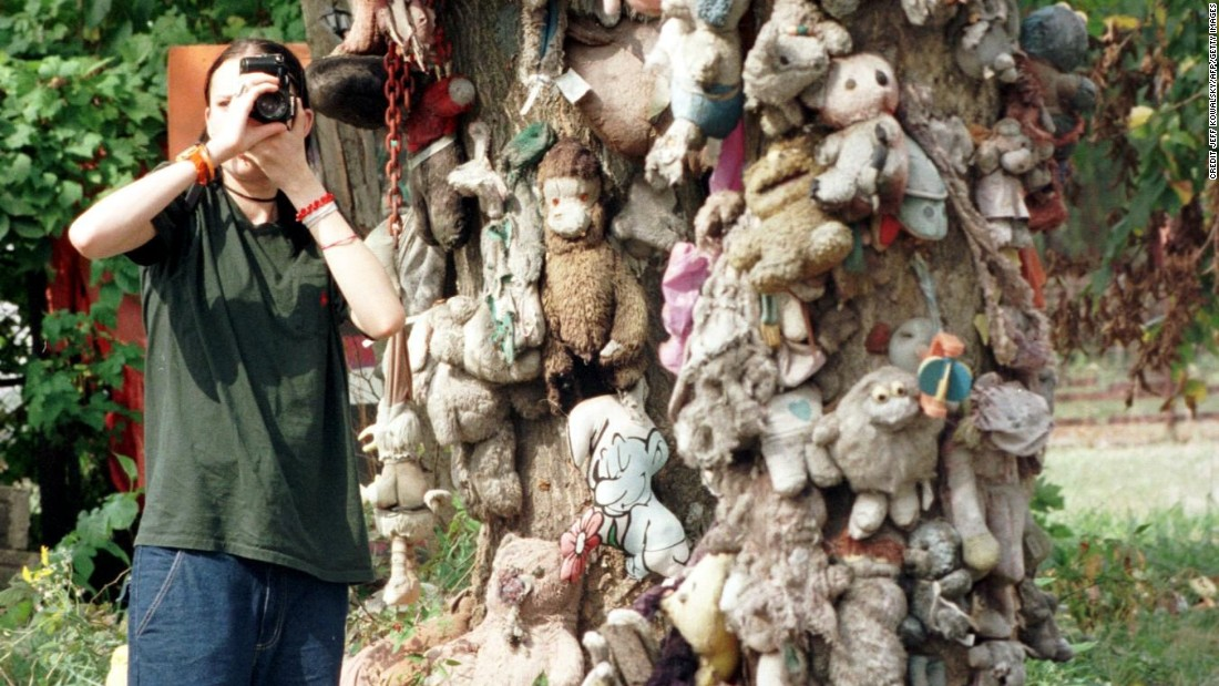 Visitor stops to take a picture of a tree adorned with stuffed animals in an abandoned neighborhood.
