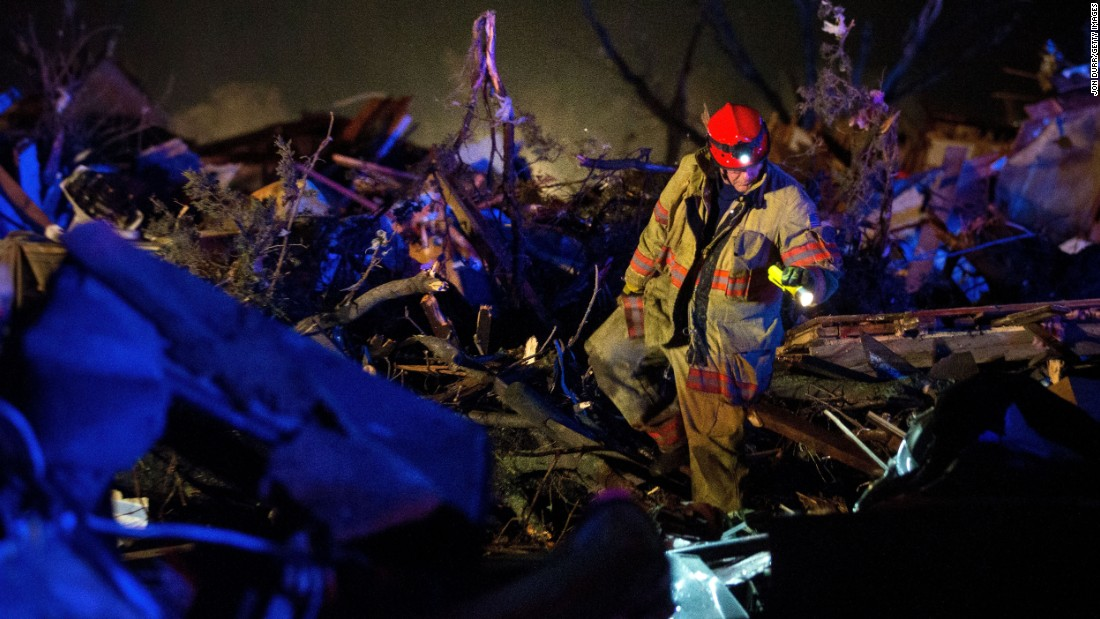 A rescue worker searches through wreckage in Fairdale on Thursday, April 9.