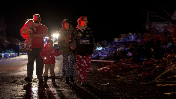 A family surveys the wreckage in Fairdale on April 9.