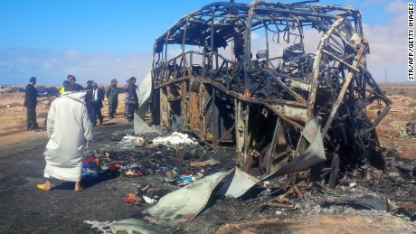 Officials check out the remains of a bus following a fire and fatal crash Friday near Tan-Tan, Morocco.