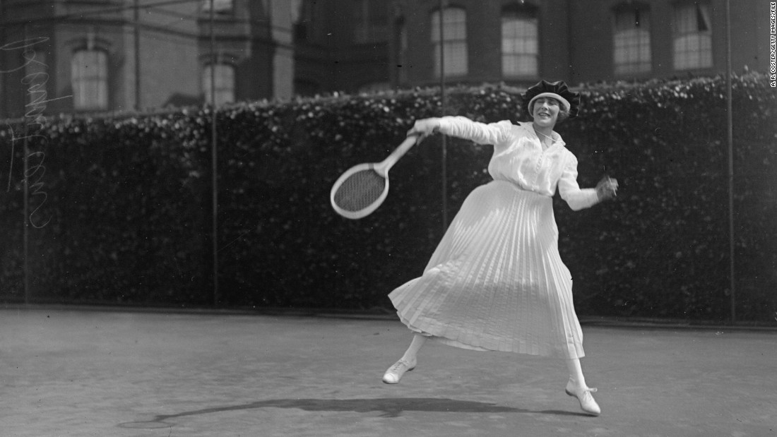"A young lady enjoys a hit at the Queen's Club lawns in London, 1918, dressed in a long pleated skirt and stockings.<br />""Tennis started out in the Victorian era in England as a lawn sport for the aristocracy,"" says Rothenberg.<br />""It would be something that happened at social occasions; people would string up a net just in the front lawn of their manor, and they would play in fairly similar attire to what they were wearing at the time."""