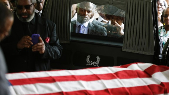 Mourners look on as the casket of Walter Scott is removed from a hearse for his funeral at W.O.R.D. Ministries Christian Center, April 11, 2015 in Summerville, South Carolina. Scott was killed by a North Charleston police officer after a traffic Saturday, April 4, 2015. The officer, Michael Thomas Slager, has been charged with murder.