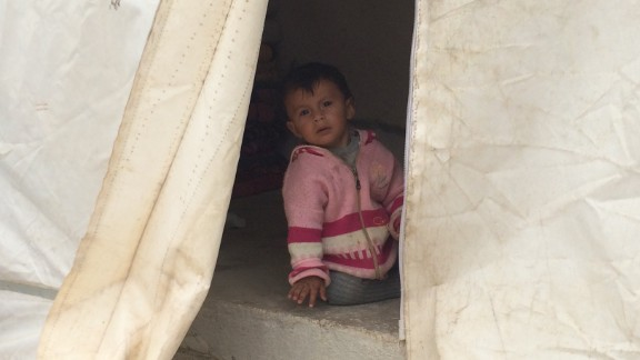 A small child is seen within the safety of a tent at the refugee camp. It