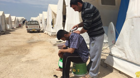 A man gives another a shave. For many, an element of normalcy has returned after months in the camp.