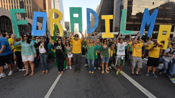 """Demonstrators hold letters reading """"Dilma out"""" during a protest against the government of president Dilma Rousseff."""