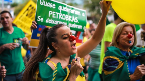 """Many demonstrators wore the country's colors -- green, blue and yellow -- waved flags, and chanted: """"Out Dilma."""""""