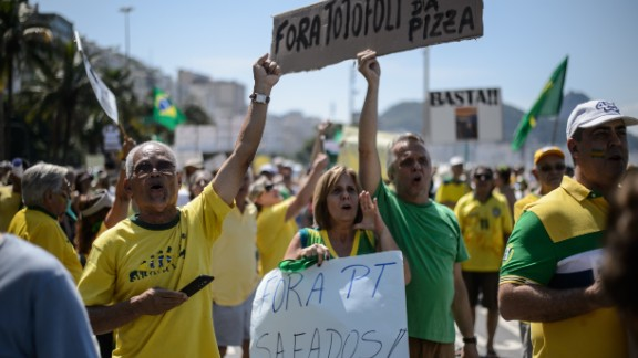 """People hold signs reading """"Workers' Party out"""" at Copacabana beach."""