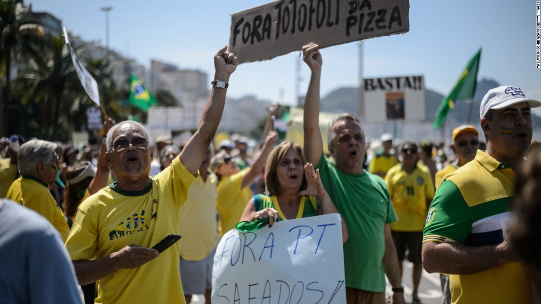 "People hold signs reading ""Workers' Party out"" at Copacabana beach."