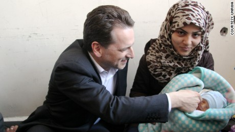 Pierre Krähenbühl touches the cheek of Jihad Ya'qoub, who was born on March 30, 2015.  His mother is Said Fatima.