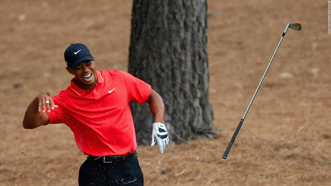 Woods winces in pain after striking a tree root with his club after a shot from the rough in the final round of the 2015 Masters Tournament in April. He tied for 17th place.
