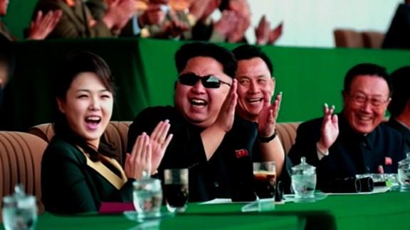 A jovial Kim Jong Un is seen clapping at a soccer match, alongside his wife Ri Sol Ju. It