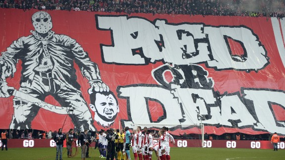 Standard de Liege fans display a banner featuring an illustration depicting the decapitation of Anderlecht midfielder Steven Defour before the Jupiler Pro League match between Standard de Liege and RSC Anderlecht, in Liege on January 25, 2015, on day 23 of the Belgian soccer championship. Fans of Belgian giants Standard Liege caused outrage when they unfurled a banner showing a mocked-up image of former captain Steven Defour being beheaded.