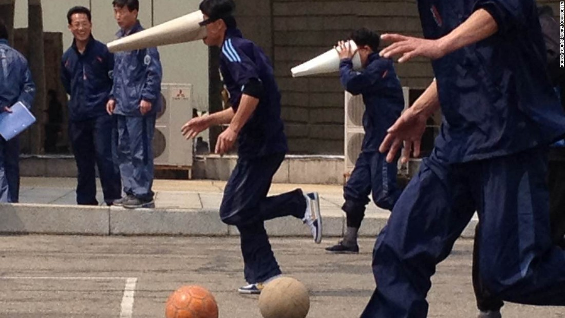 Yanggakdo hotel workers wearing conical masks play a game on April 15.