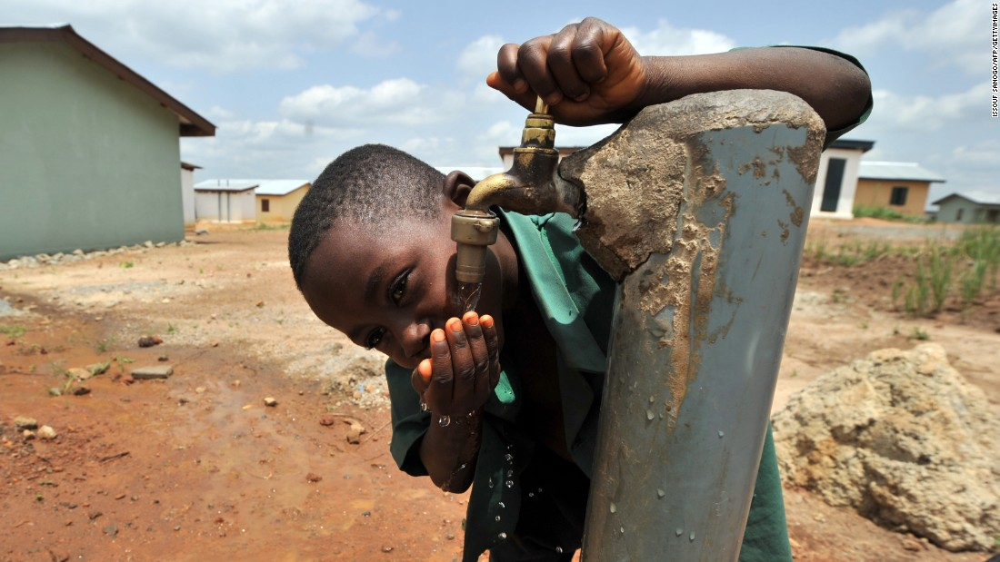 A boy drinks water from a tap in eastern Sierra Leone in April 2012 in a new town that provides access to clean drinking water, education and training.