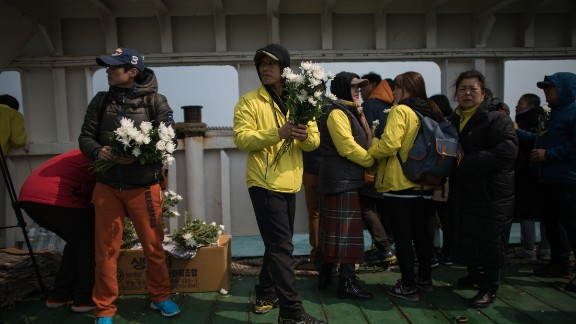A relative hands out flowers to others on the deck of a boat during a visit to the site of the sunken ferry. More than 100 relatives of victims of South Korea