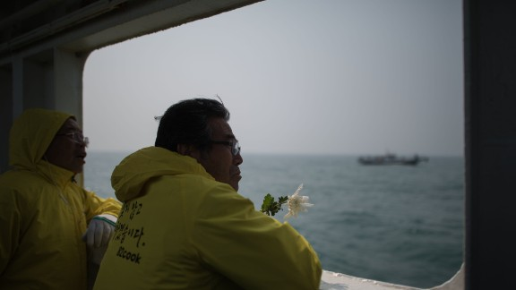 A man hold a flower as he stands on the deck of a boat during a visit to the site of the sunken Sewol ferry, off the coast of South Korea