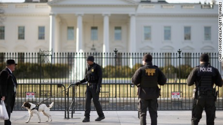 A US Secret Service K-9 team works along the second, temporary fence on the north side of the White House March 18, 2015, in Washington.