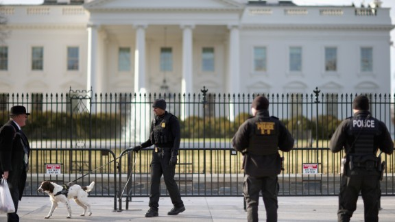 A U.S. Secret Service K-9 team works along the second, temporary fence on the north side of the White House March 18, 2015 in Washington, D.C.
