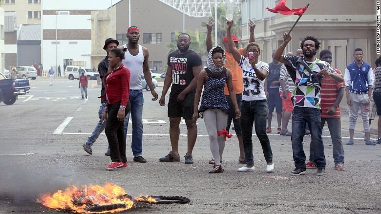 Foreign nationals gesture after clashes broke out between a group of locals and police in Durban on April 14 ,2015 in ongoing violence against foreign nationals in Durban, South Africa. The attacks on immigrant-owned shops and homes in Durban's impoverished townships come three months after a similar spate of attacks on foreign-owned shops in Soweto, near Johannesburg. The Malawian government said on April 13, 2015 it would help repatriate its citizens from South Africa following an outbreak of xenophobic violence in the eastern port city of Durban that has left four people dead.
