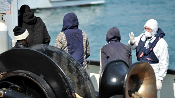 An Italian coast guard looks at people disembarking from the tanker Maria Bottiglieri, during the landing operations of more than 110 Central African migrants, men and women, on April 15, 2015 in the port of Corigliano Calabro.