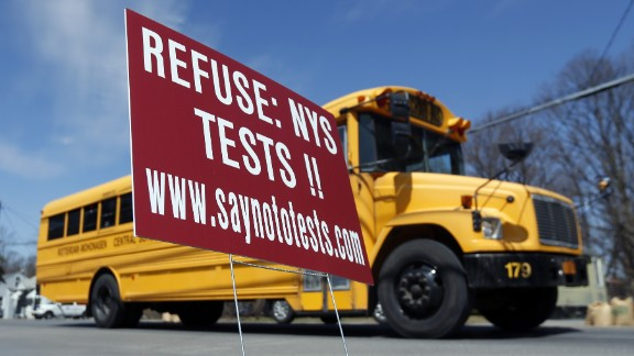 A school bus passes a sign encouraging parents to refuse that their children take state tests on Monday, April 13 in Rotterdam, N.Y. With standardized English tests set to begin Tuesday in New York schools, some parents are again planning to have their children sit out the exams.