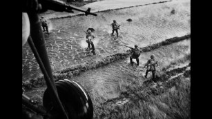 South Vietnamese troops wade through water to flush out communist rebels, known as the Viet Cong, in 1962. Several years earlier, North Vietnamese communists began helping the Viet Cong fight South Vietnamese troops. They wanted to overthrow the South Vietnamese government and reunite the country, which split in 1954.