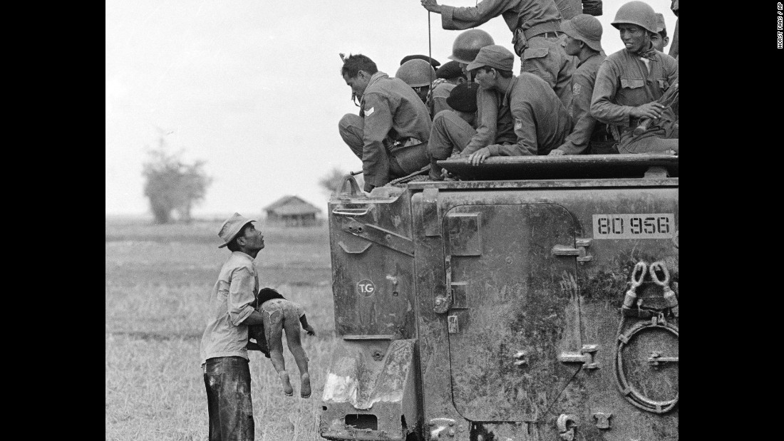 A father holds the body of his child as South Vietnamese Army Rangers look down from their armored vehicle in March 1964. The child was killed as government forces pursued guerrillas into a village near the Cambodian border.