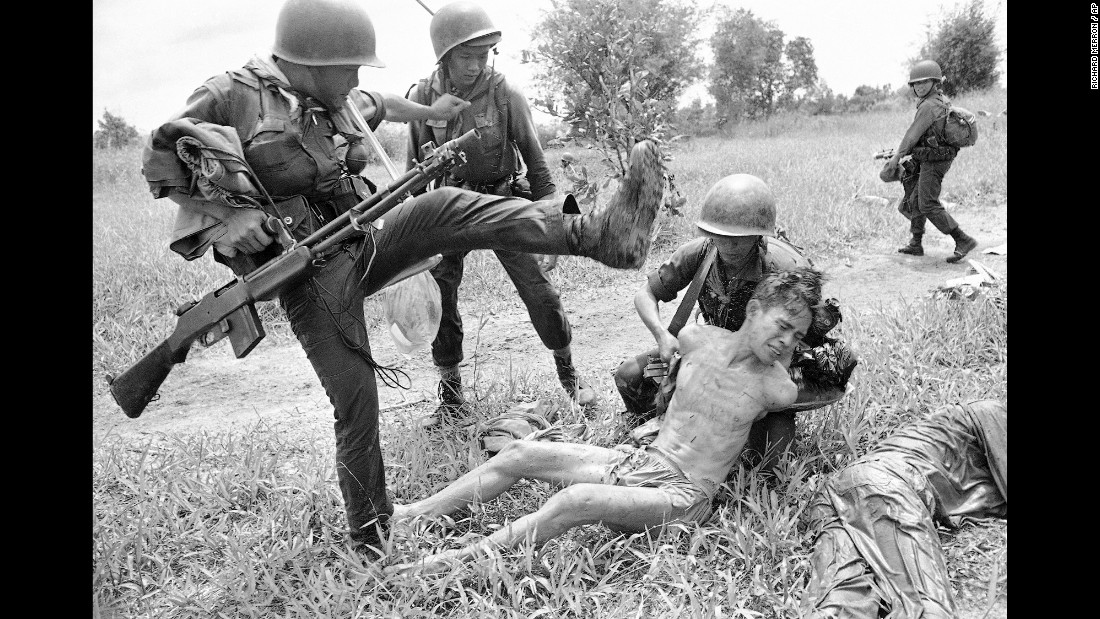 A suspected Viet Cong is kicked by a South Vietnamese soldier in October 1965. The prisoner was one of 15 captured in a raid near Xom Chua.