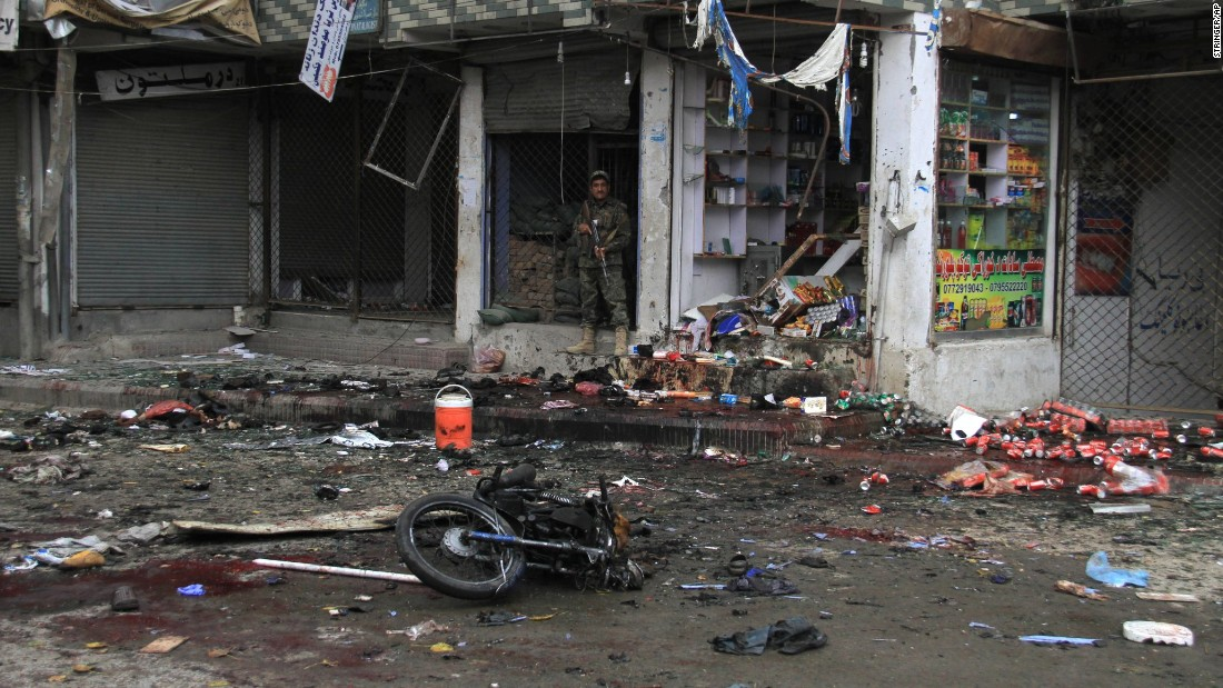 A member of Afghanistan's security forces stands at the site where a suicide bomber on a motorbike blew himself up in front of the Kabul Bank in Jalalabad, Afghanistan, on Saturday, April 18. ISIS claimed responsibility for the attack. The explosion killed at least 33 people and injured more than 100 others, a public health spokesman said.