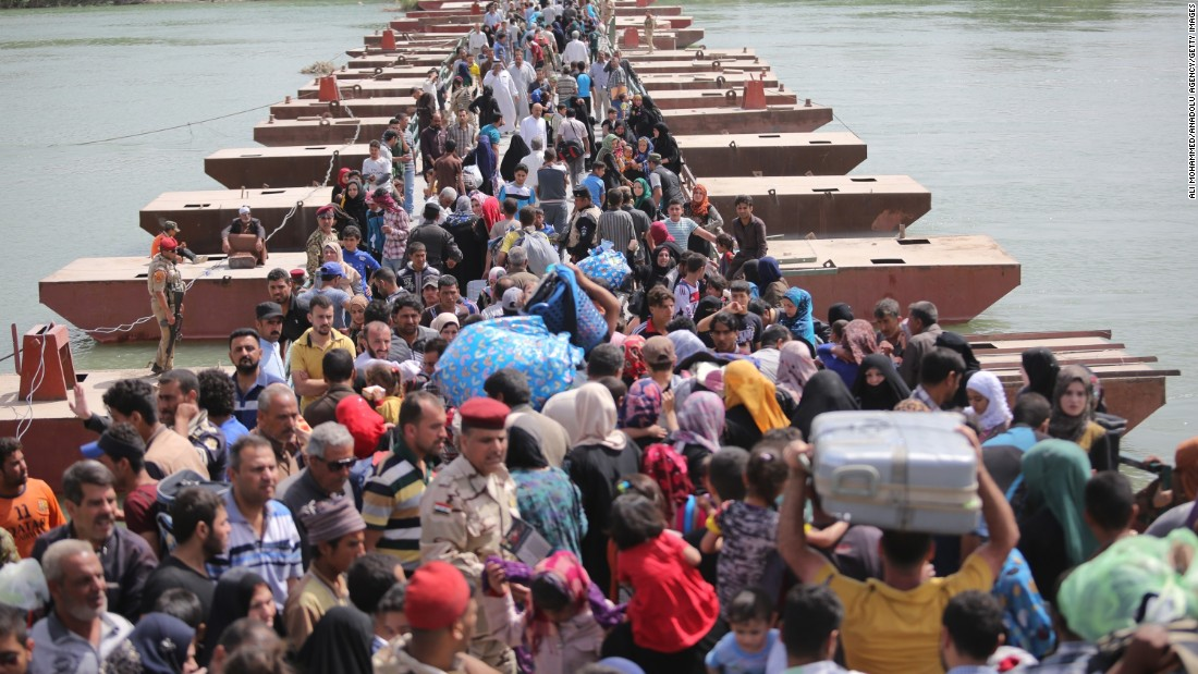 Thousands of Iraqis cross a bridge over the Euphrates River to Baghdad as they flee Ramadi on Friday, April 17.