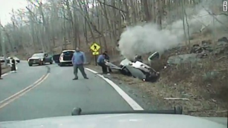 Woman rescued from overturned car before it explodes