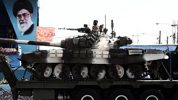 A soldier sits atop a T-72 tank as it rolls past a portrait of Supreme Leader Ayatollah Ali Khamenei on April 18.