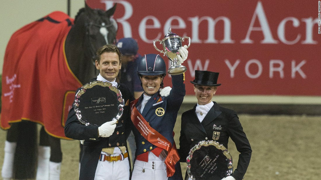 The 29-year-old Dujardin lifts the winner's trophy alongside second placed Dutch rider Edward Gal (L) and Germany's Jessica von Bredow-Werndl in third (R).