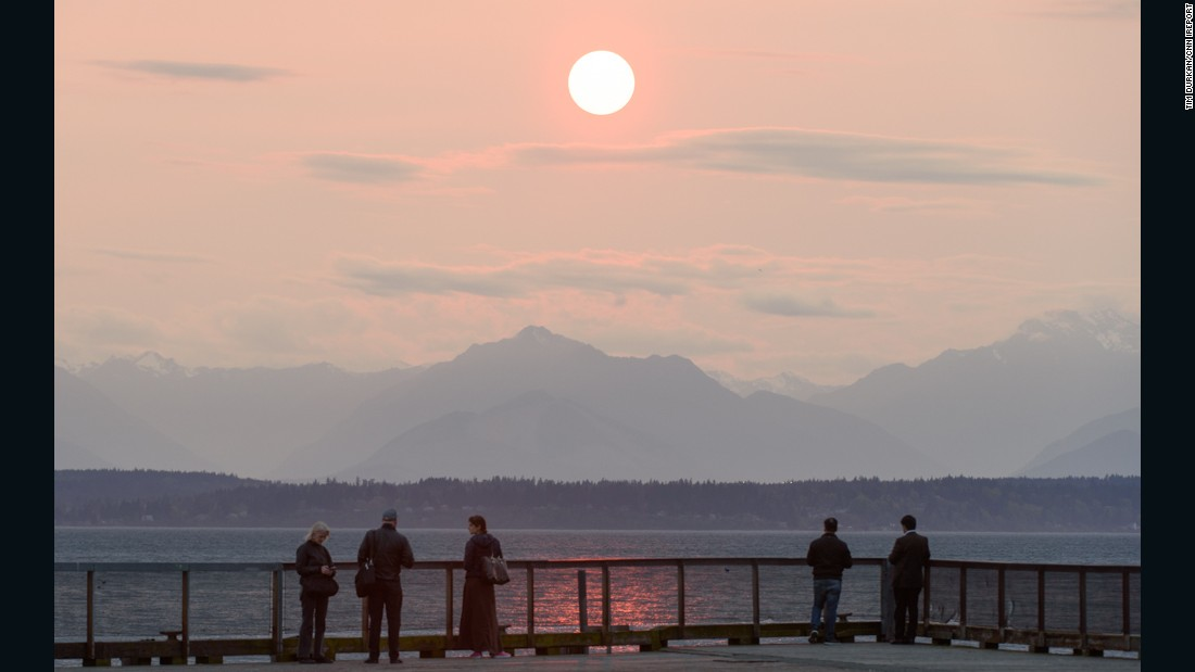People in Seattle gather on a boardwalk to admire the sunset on Sunday.