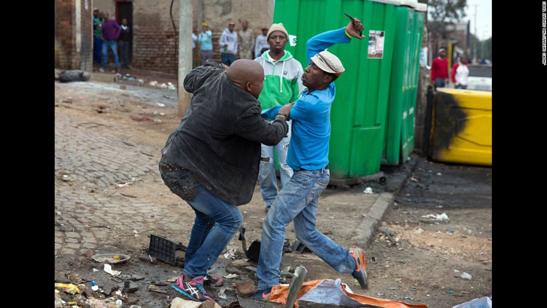 Mozambican Emmanuel Sithole, left, was walking down a street in Johannesburg's Alexandra Township when four men surrounded him on Saturday, April 18. Sithole pleaded for mercy, but it was already too late. The attackers bludgeoned him with a wrench and stabbed him with knives, killing him in broad daylight. Photographer James Oatway was nearby and captured it all on his camera.