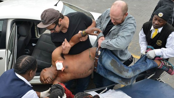 Another photographer, Antoine de Ras, captured the moment Oatway and local authorities assisted the victim. Oatway is the one holding Sithole