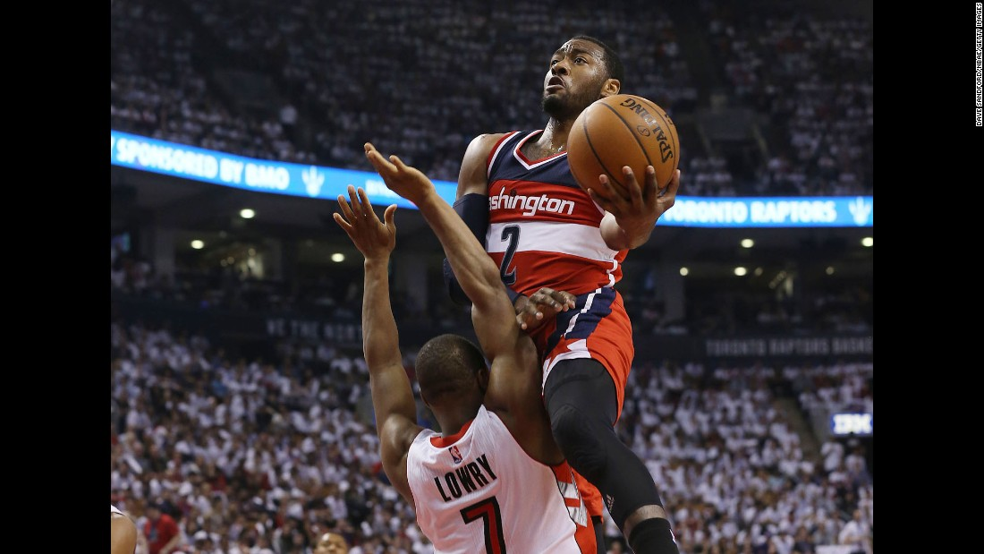 Washington's John Wall leaps into Toronto's Kyle Lowry as he drives to the basket Saturday, April 18, during Game 1 of their Eastern Conference playoff series. Wall and the Wizards defeated the Raptors 93-86 in overtime.