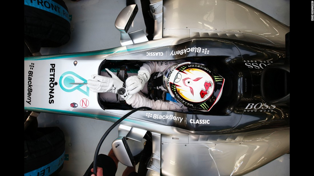 Formula One driver Lewis Hamilton adjusts his suit Friday, April 17, as he prepares for the Bahrain Grand Prix in Sakhir, Bahrain. He won the race two days later.