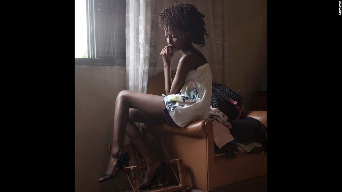 Maysa perches on the armrest of a chair in her home. She lives in the Brasilândia slum on the edge of São Paulo.