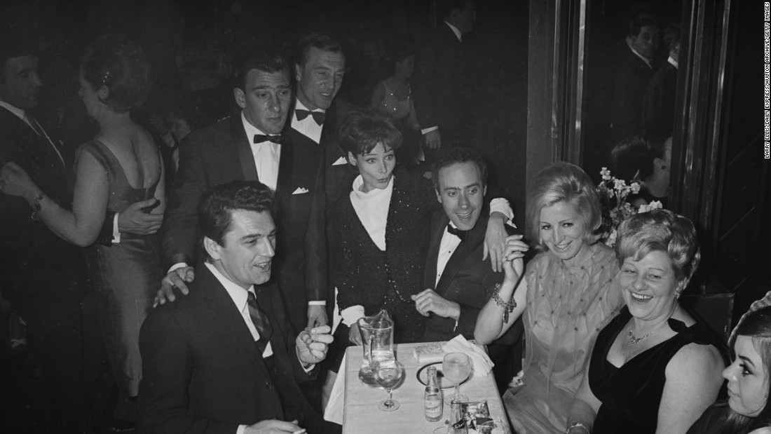 Frances Shea (1943 - 1967, far right) with her husband, English gangster Reggie Kray (1933 - 2000, standing, third from left) and celebrity guests at the El Morocco, a nightclub owned by the Kray Twins, in Soho, London, 30th April 1965. Kray has his hand on the shoulder of British actor Edmund Purdom (1924 - 2009). At centre is Actress Adrienne Corri with her arm around Welsh actor Victor Spinetti (1929 - 2012). The Kray twins' mother, Violet Kray, is second from right.