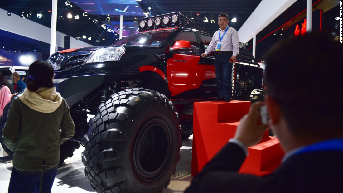 A man poses next to a monster pick-up truck made by Chinese company Foton Motor  at the Shanghai Auto Show on April 20, 2015.