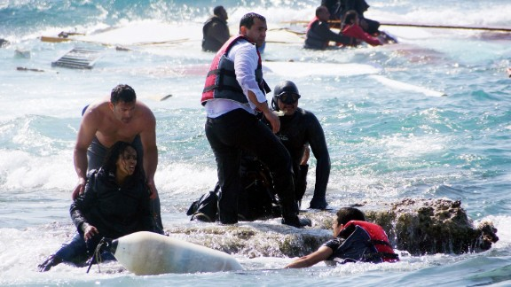 Caption:Local residents and rescue workers help a migrant woman after a boat carrying migrants sank off the island of Rhodes, southeastern Greece, on April 20, 2015. At least three people, including a child, died when a boat carrying more than 80 migrants sank off the Greek island of Rhodes today, police said. AFP PHOTO / EUROKINISSI / ARGIRIS MANTIKOS (Photo credit should read ARGIRIS MANTIKOS/AFP/Getty Images)