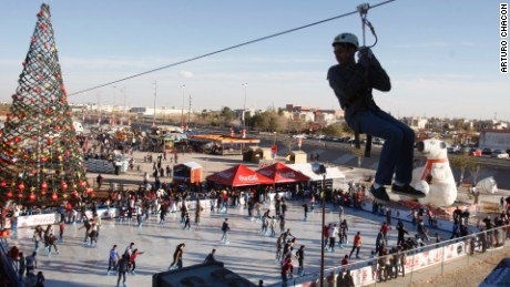 An ice rink in Ciudad Juarez, Mexico, is crowded with skaters as a zip liner passes overhead.
