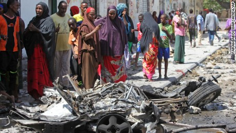 Somalis stand over the wreckage of a car bomb in Mogadishu.