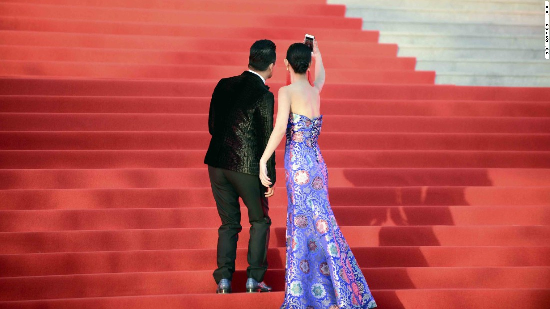 Two people take a selfie on the red carpet while attending the Beijing International Film Festival on Thursday, April 16.
