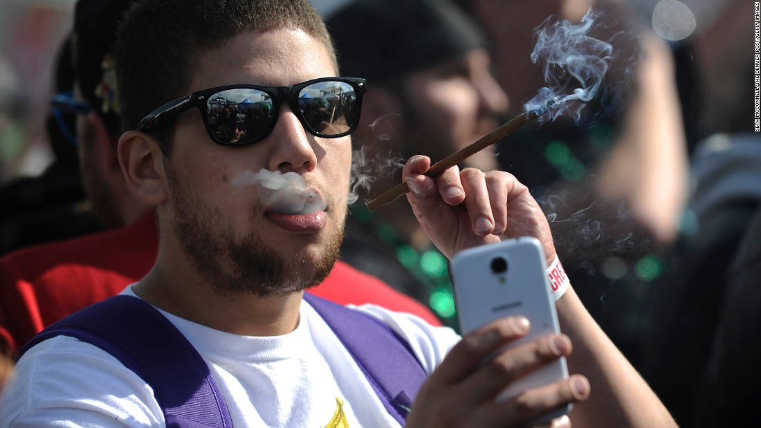A man takes a selfie Sunday, April 19, as he smokes marijuana during the High Times Cannabis Cup, a trade show that took place in Denver.