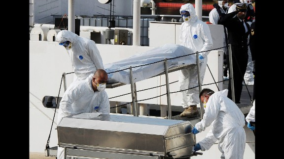 Italian Coast Guard officers carry the body of a dead migrant off a ship in Valletta, Malta, on April 20. A smuggler