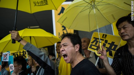 Pro-democracy protesters hold yellow umbrellas, a symbol of Hong Kong's Occupy movement, during a demonstration outside the city's Legislative Council on April 22, 2015.