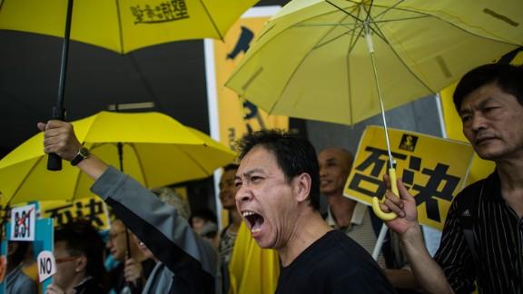 Pro-democracy protesters hold yellow umbrellas, a symbol of Hong Kong